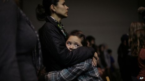 Nine-year-old Raelynn Holloway, hugs her mother Rhiannon Holloway, left, during a prayer vigil for the victims of the Berrendo Middle School shooting in Roswell, New Mexico 14 January 2014