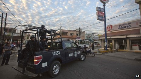 Federal police outside vandalised pharmacy in Apatzingan