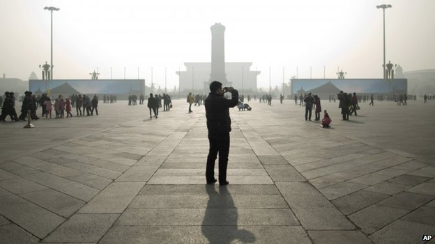 A tourist takes photos during a heavily polluted day on Tiananmen Square in Beijing on 16 January 2014