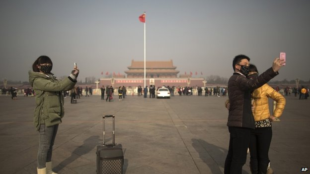 Tourists in masks use mobile phone cameras to snap shots of themselves during a heavily polluted day on Tiananmen Square in Beijing, China, 16 January 2014
