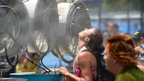 A woman cools off with fans and mist put out for spectators as a heat wave continues to sizzle on day three of the Australian Open