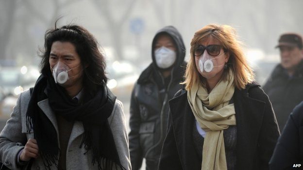People wearing face masks walk along a street in Beijing on 16 January 2014