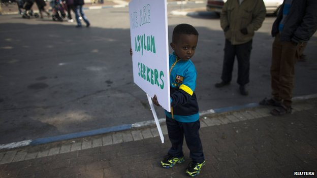 A child from the African migrant community holds a placard ahead of a protest against Israel's detention policy toward migrants, in Tel Aviv (15 January 2014)