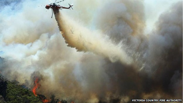 A helicopter flies above a fire in the Northern Grampians, Victoria, Australia, 17 January 2014