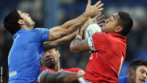 Tonga's Nesiasi Mataitonga (r) and Italy's Anthony Minichiello challenge for the ball