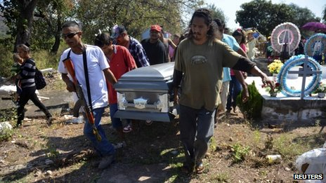 Family members, friends and a vigilante carry the coffin of Mario Perez at a cemetery in Antunez January 15, 2014.