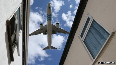 A passenger jet comes into land over houses near to London's Heathrow airport