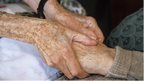 Carer holding elderly person's hands