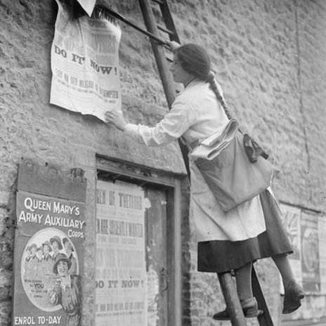 A young girl on a step ladder putting up posters on a wall