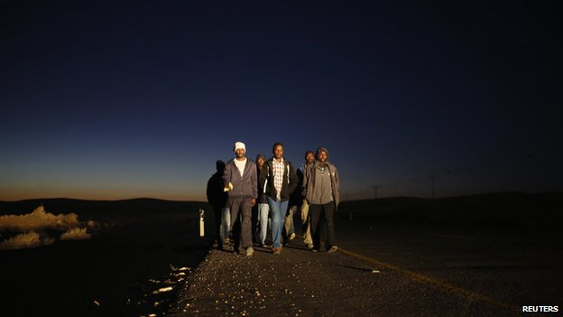 African migrants walk on a road after abandoning a detention facility in the southern Israeli desert (December 15, 2013)