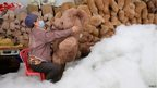 A worker stuffs a toy bear with cotton at a toy factory in Wuhan, China