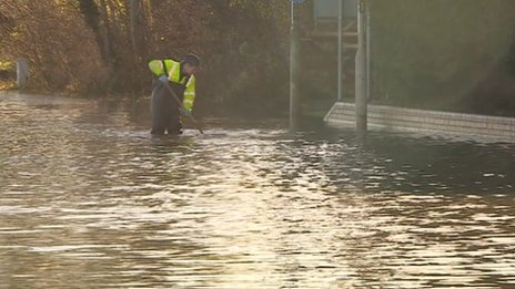 A workman knee deep in flood water