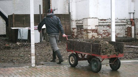 Man with truck of rubbish