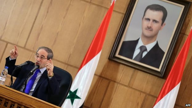 Syrian Deputy Foreign Minister Faisal Mekdad addresses reporters in front of a portrait of Bashar al-Assad (4 November 2013)
