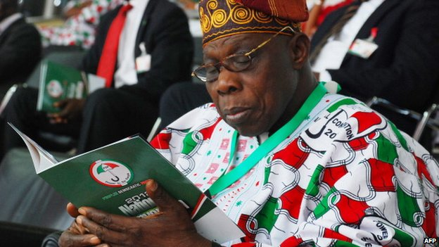 Nigeria's former President Olusegun Obasanjo reads the programme during the People's Democratic Party (PDP) party convention in Abuja on 24 March 2012