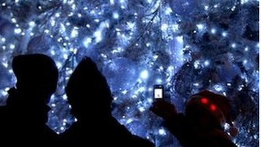 Outline of family taking photo of Christmas tree
