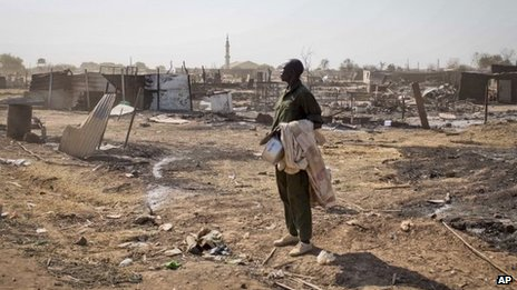 A man carrying his belongings looks at destroyed buildings in Bentiu. Photo: 12 January 2014