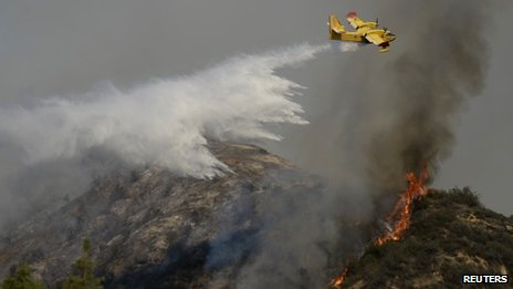 "A ""super scooper"" air tanker makes waters drops as firefighters battle a fast-moving California wildfire, so-called the ""Colby Fire"", in the hills of Glendora 16 January 2014"