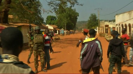 An African Union soldier defends a Muslim man from Christian militiamen