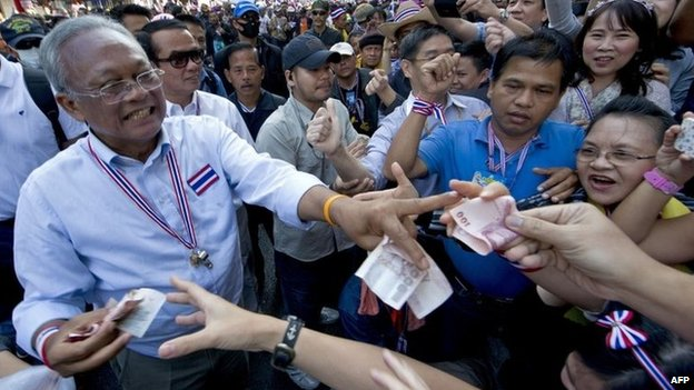 Thai protest leader Suthep Thaugsuban (L) receives donations from supporters during a rally in Bangkok on 17 January 2014