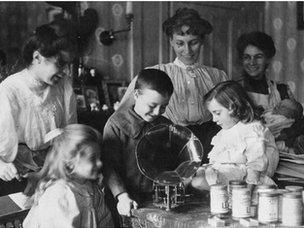 Three women and children gathered around a gramophone at home during World War One