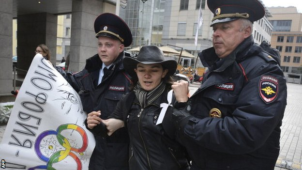 A protester is led away by Russian police officers