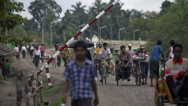 In this Sept. 14, 2013 photo, Muslims travel past a road barrier next to a security checkpoint in Maungdaw, northern Rakhine state, Myanmar.