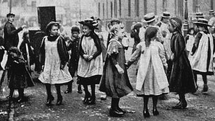 Girls in a London street dance to the music of a barrel organ
