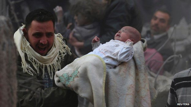 Man carries a baby who survived an alleged air strike by government forces on the Duma neighbourhood of Damascus on 7 January 2014