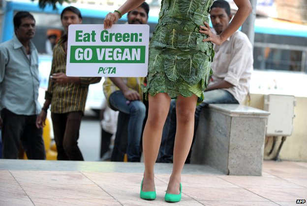 "A PETA activist in India holds a sign reading ""Eat Green: Go vegan"""