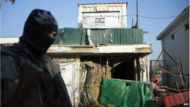 An Afghan policeman stands guard next to the damaged entrance of a Lebanese restaurant that was attacked in Kabul, on January 18