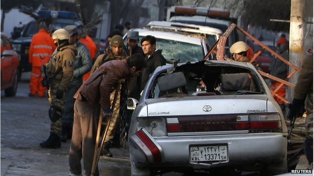 Fawad, a worker of a Lebanese restaurant who was injured during a suicide bombing attack outside the restaurant, looks at a damaged vehicle near the restaurant in Kabul, January 18