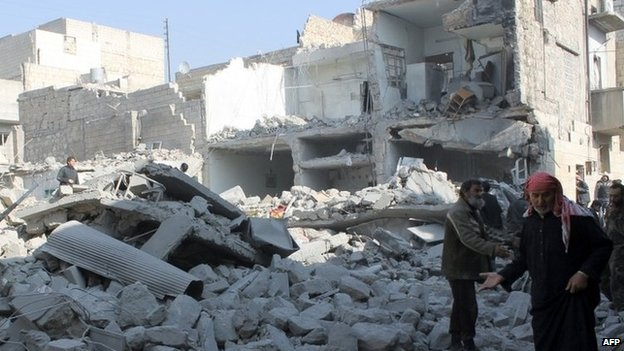 Syrians inspect damaged buildings in Aleppo. Photo: 18 January 2014