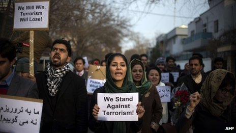 Afghan activists pay tribute to the victims of an attack two days ago, in front of the restaurant on 19 January 2014