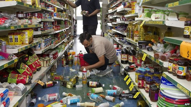 Staff members clear stock knocked off the shelves by the earthquake from their shop floor in the Wairarapa town of Eketahuna on 20 January 2014