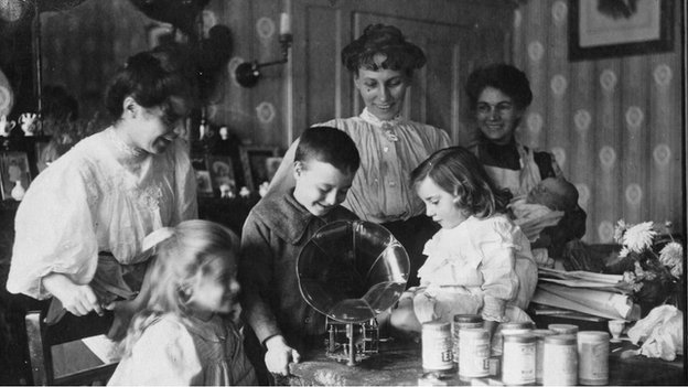 A family of adult women and children gather round the gramophone in their living room