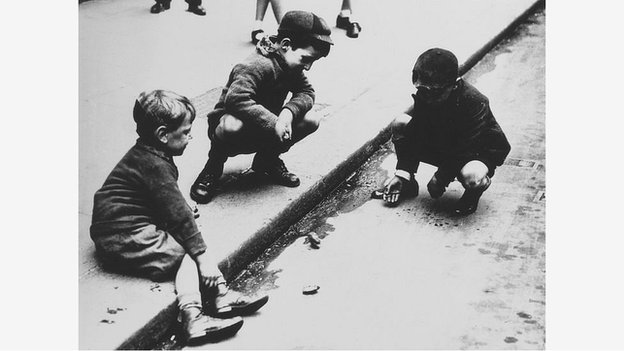 Three boys playing marbles in the gutter