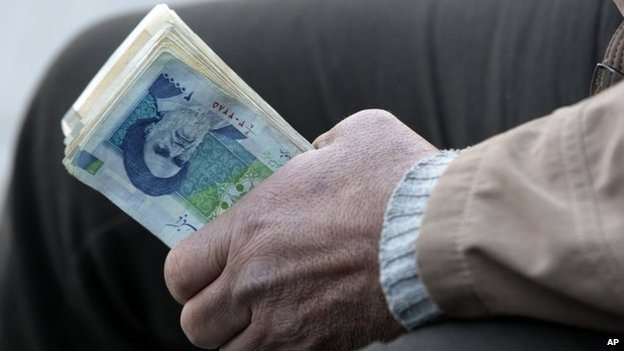 Man holds Iranian rials at Tehran's main bazaar (23 September 2013)