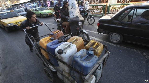 A man pushes a cart carrying fuel containers in Tehran (23 September 2013)