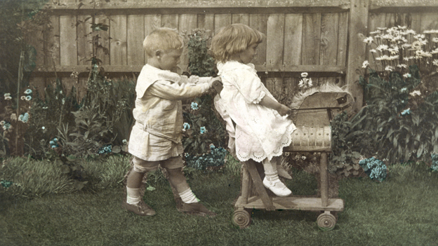 A boy and girl in their garden play on a toy horse.
