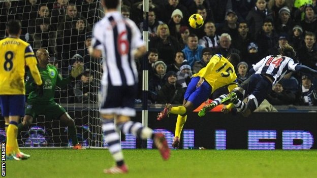 West Brom player Diego Lugano (right) dives to head the first West Brom goal