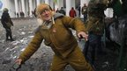 An elderly protestor prepares to throw a stone, during clashes with police, in central Kiev, Ukraine, Monday, Jan. 20, 2014