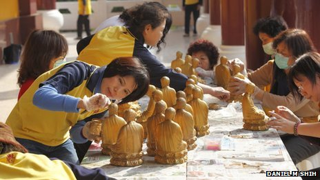 Volunteers clean Buddha statues at the Fo Guang Shan temple in Kaohsiung