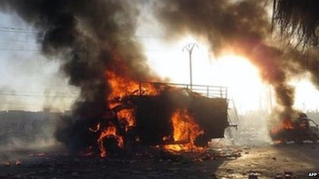 A Syrian man (left) runs next of a burned truck that was attacked by a Syrian forces helicopter in Aleppo (18 January 2014)