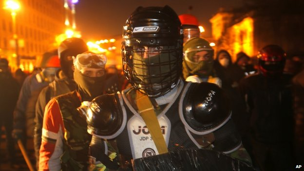 Protesters clad in improvised protective gear prepare for a clash with police in central Kiev, Ukraine, late on Monday 20 January 2014