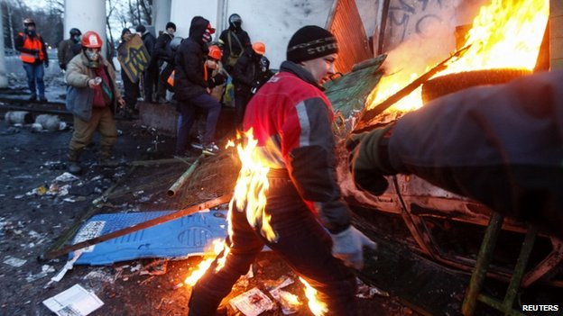 A protester catches fire during clashes with police in Kiev on Monday