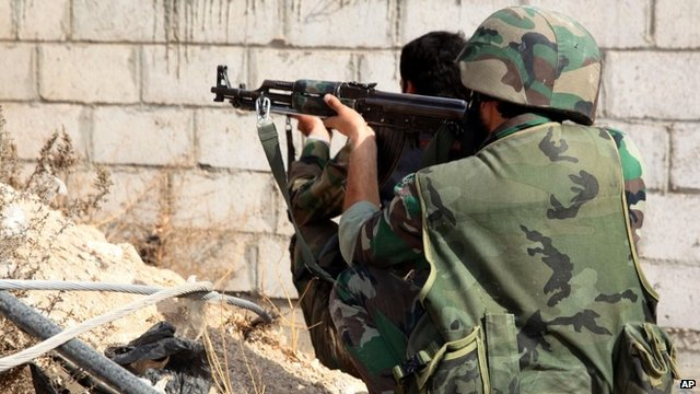 Syrian army soldiers take their positions on a street in Sabina suburb, south of Damascus, Syria in Nov 2013