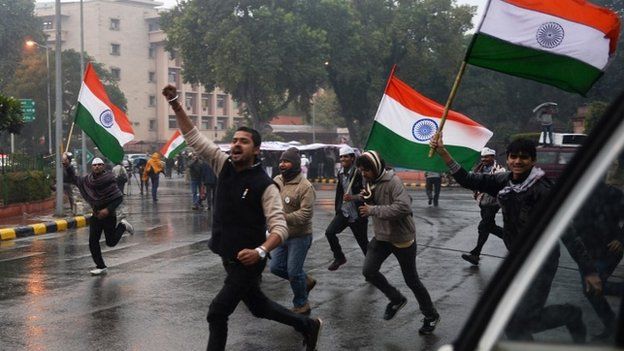 Supporters of New Delhi chief minister, Arvind Kejriwal carry Indian flags as they run close to the area where Kejriwal spent the night during a sit-in protest in New Delhi on January 21, 2014
