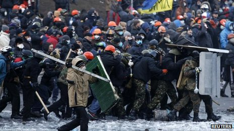 Pro-European integration protesters approach riot police during clashes in Kiev