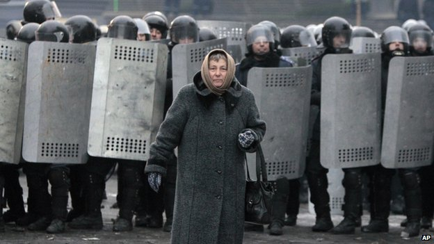 An elderly woman walks away from police officers as they block a street during unrest in central Kiev, Ukraine, on Tuesday 21 January 2014